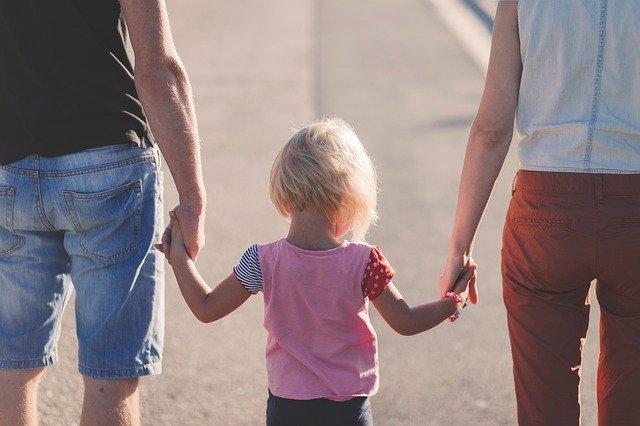 Criança de mãos dadas com os pais