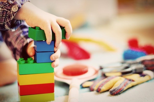 mão de criança brincando com lego